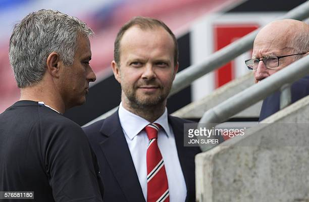 Manchester United's executive vicechairman Ed Woodward listens as Manchester United's Portuguese manager Jose Mourinho talks with former Manchester...