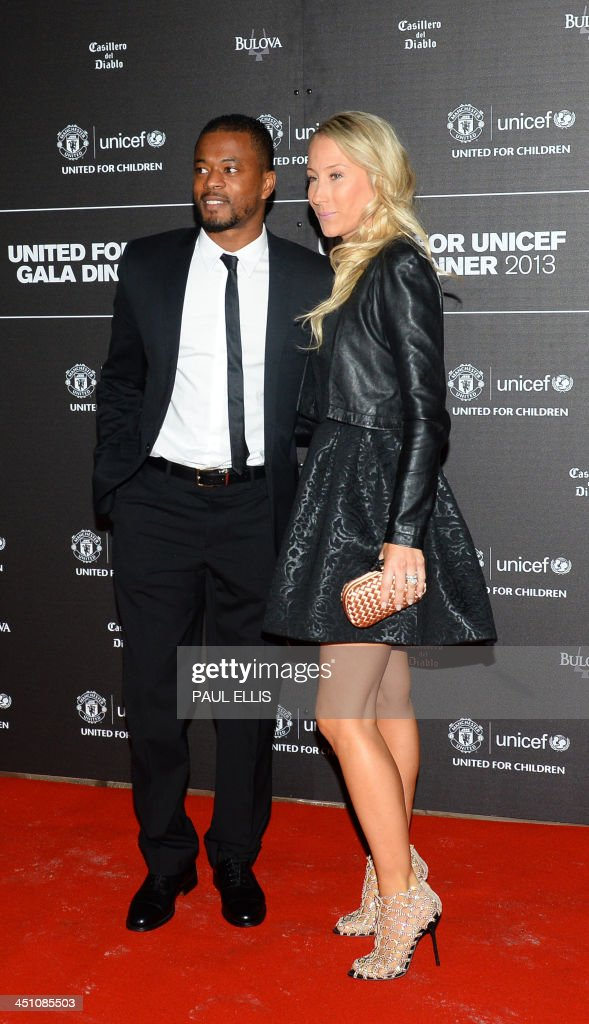 Manchester United's French defender Patrice Evra (L) ad his wife Sandra pose for photographs as the arrive for a gala dinner in aid of UNICEF at Old Trafford in Manchester on November 21, 2013.