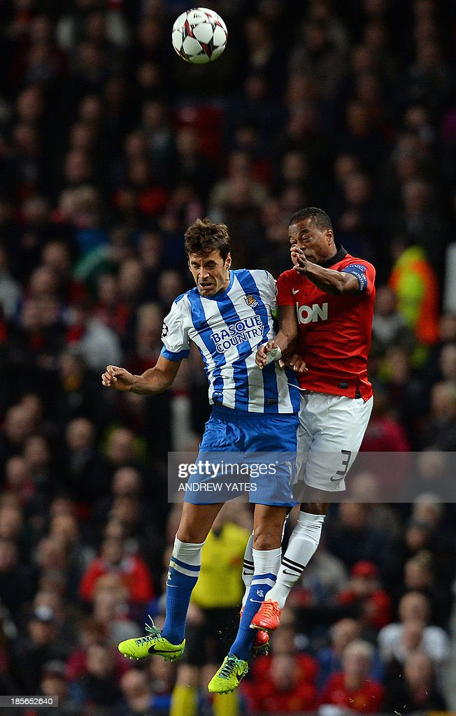 Manchester United's French defender Patrice Evra (R) and Real Sociedad's midfielder Xabi Prieto jump for the ball during the UEFA Champions League football match between Manchester United and Real Sociedad at Old Trafford in Manchester, north west England on October 23, 2013.