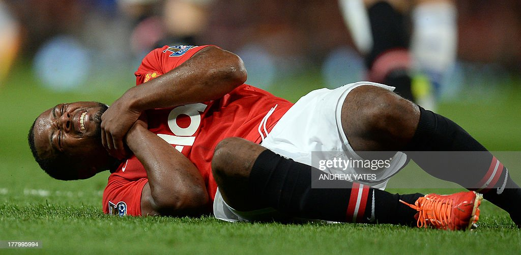 Manchester United's French defender Patrice Evra holds his throat injured on the floor during the English Premier League football match between Manchester United and Chelsea at Old Trafford in Manchester, northwest England, on August 26, 2013. USE. No use with unauthorized audio, video, data, fixture lists, club/league logos or live services. Online in-match use limited to 45 images, no video emulation. No use in betting, games or single club/league/player publications.