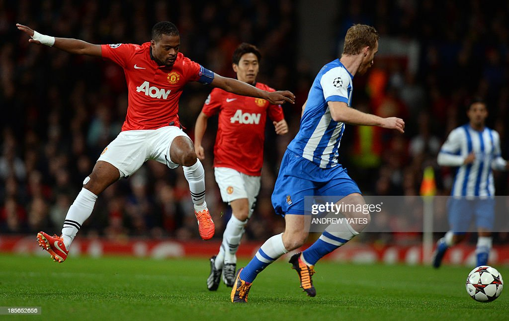 Manchester United's French defender Patrice Evra (L) jumps during the UEFA Champions League football match between Manchester United and Real Sociedad at Old Trafford in Manchester, north west England on October 23, 2013.