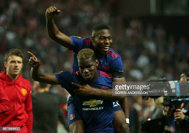 Manchester United's French midfielder Paul Pogba amd Manchester United's Dutch defender Timothy FosuMensah celebrate after the UEFA Europa League...