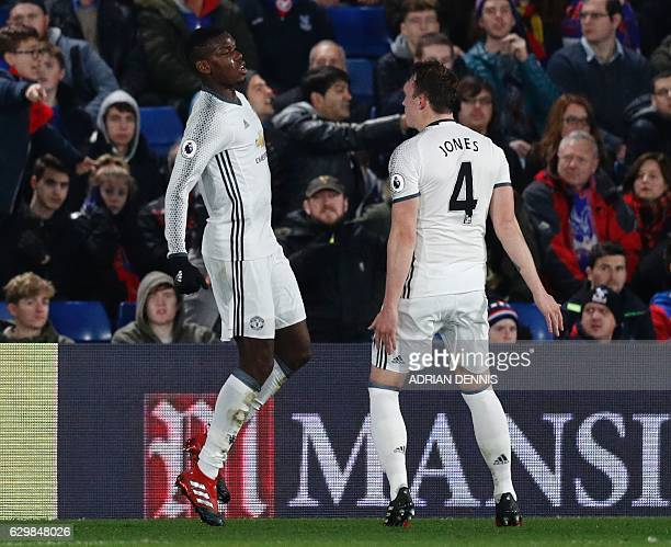 Manchester United's French midfielder Paul Pogba celebrates scoring the opening goal with Manchester United's English defender Phil Jones during the...
