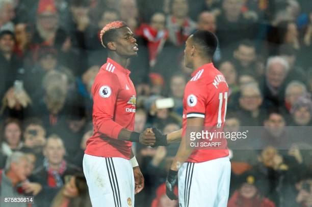 Manchester United's French midfielder Paul Pogba celebrates scoring their third goal with Manchester United's French striker Anthony Martial during...