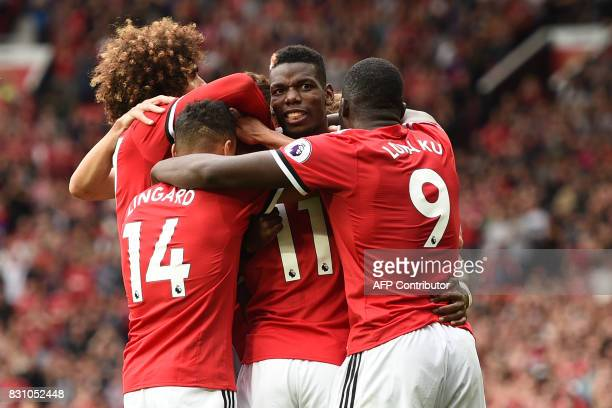 Manchester United's French midfielder Paul Pogba celebrates with teammates after scoring their fourth goal during the English Premier League football...