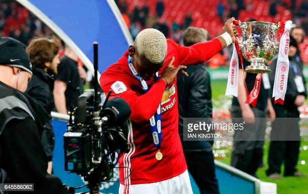 Manchester United's French midfielder Paul Pogba celebrates with the trophy on the pitch after their victory in the English League Cup final football...