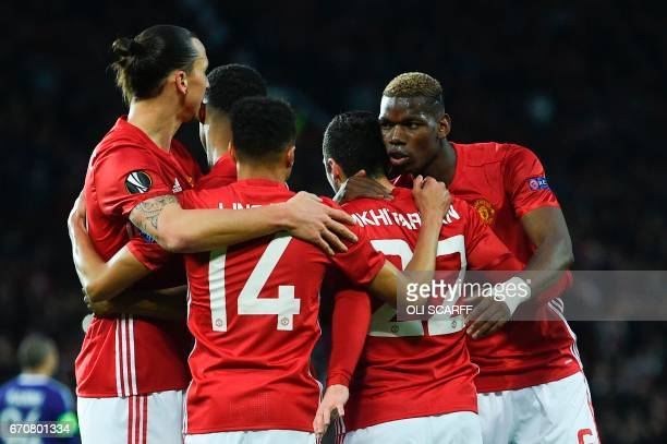 Manchester United's French midfielder Paul Pogba congratulates Manchester United's Armenian midfielder Henrikh Mkhitaryan on his opening goal during...