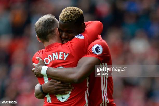 TOPSHOT Manchester United's French midfielder Paul Pogba embraces Manchester United's English striker Wayne Rooney after scoring their second goal...