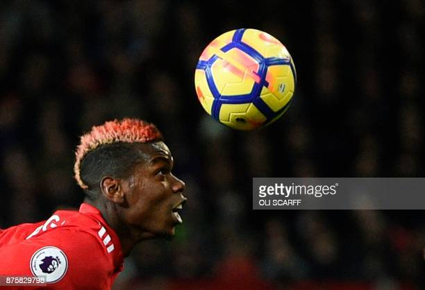 Manchester United's French midfielder Paul Pogba goes for a header during the English Premier League football match between Manchester United and...