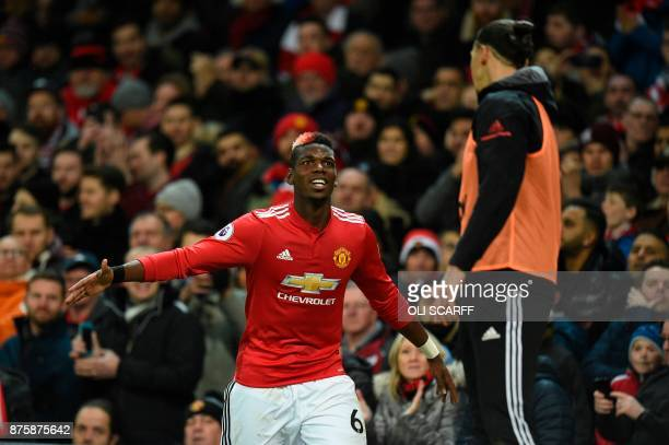 Manchester United's French midfielder Paul Pogba greets Manchester United's Swedish striker Zlatan Ibrahimovic as Pogba leaves the pitch substituted...