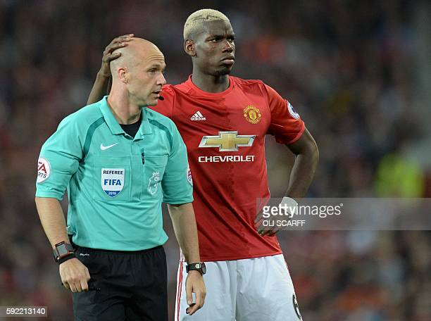 Manchester United's French midfielder Paul Pogba shares a moment with referee Anthony Taylor during the English Premier League football match between...