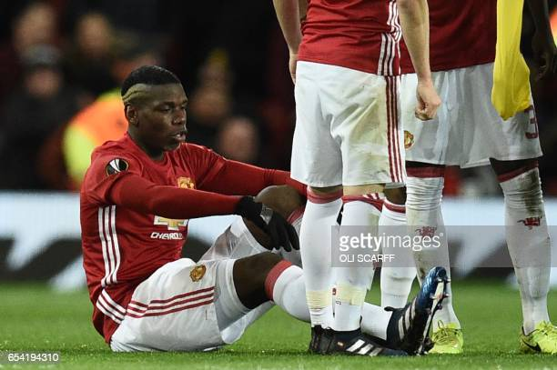 Manchester United's French midfielder Paul Pogba sits on the pitch injured during the UEFA Europa League round of 16 secondleg football match between...