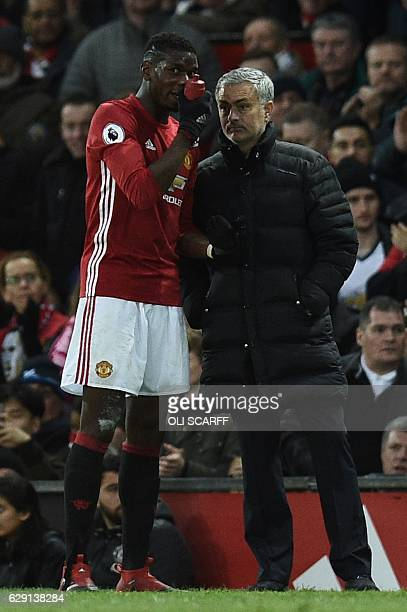 Manchester United's French midfielder Paul Pogba speaks to Manchester United's Portuguese manager Jose Mourinho during the English Premier League...