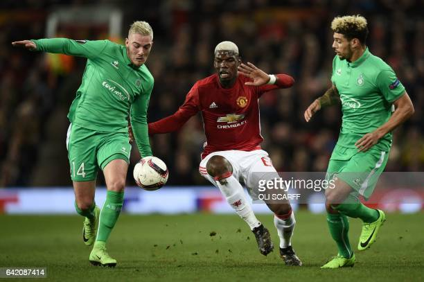 Manchester United's French midfielder Paul Pogba vies with SaintEtienne's French midfielder Jordan Veretout and SaintEtienne's French defender Kevin...