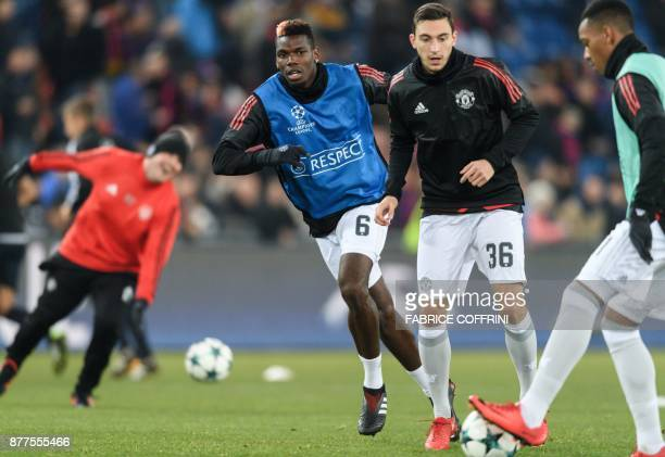 Manchester United's French midfielder Paul Pogba warms up behind Manchester United's Italian defender Matteo Darmian prior to the UEFA Champions...