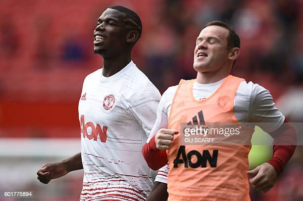 Manchester United's French midfielder Paul Pogba warms up with Manchester United's English striker Wayne Rooney ahead of the English Premier League...