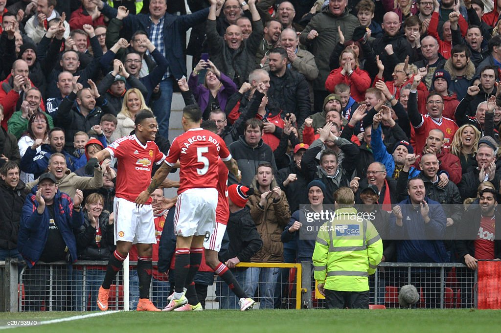 Manchester United's French striker Anthony Martial (L) celebrates scoring the opening goal during the English Premier League football match between Manchester United and Leicester City at Old Trafford in Manchester, north west England, on May 1, 2016. / AFP / OLI SCARFF / RESTRICTED TO EDITORIAL USE. No use with unauthorized audio, video, data, fixture lists, club/league logos or 'live' services. Online in-match use limited to 75 images, no video emulation. No use in betting, games or single club/league/player publications. /