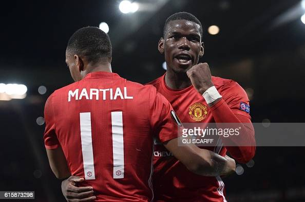 TOPSHOT Manchester United's French striker Anthony Martial embraces Manchester United's French midfielder Paul Pogba as he celebrates scoring their...