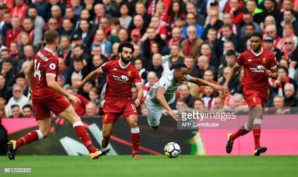 Manchester United's French striker Anthony Martial falls under a challenge from Liverpool's Egyptian midfielder Mohamed Salah during the English...