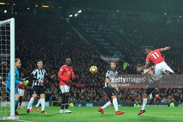 Manchester United's French striker Anthony Martial heads the ball to score an equalising goal for 11 during the English Premier League football match...