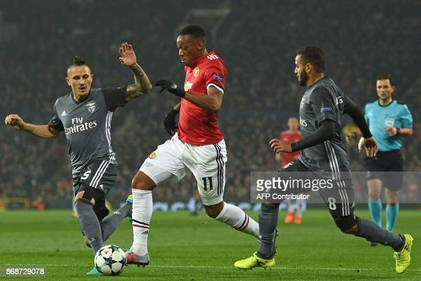 Manchester United's French striker Anthony Martial runs between Benfica's Serbian midfielder Ljubomir Fejsa and Benfica's Brazilian defender Douglas...