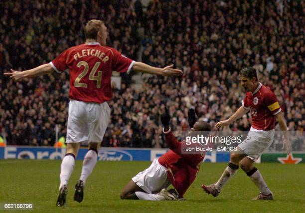 Manchester United's goal scorer Louis Saha slides on his knees celebrates with team mates Darren Fletcher and Gary Neville