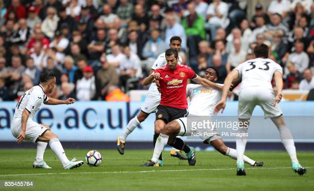 Manchester United's Henrikh Mkhitaryan battles with Swansea City's Leroy Fer and Swansea City's Roque Mesa during the Premier League match at the...