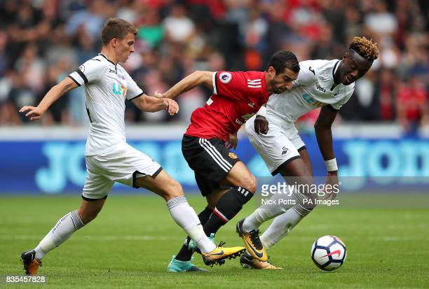 Manchester United's Henrikh Mkhitaryan battles with Swansea City's Tom Carroll and Tammy Abraham during the Premier League match at the Liberty...