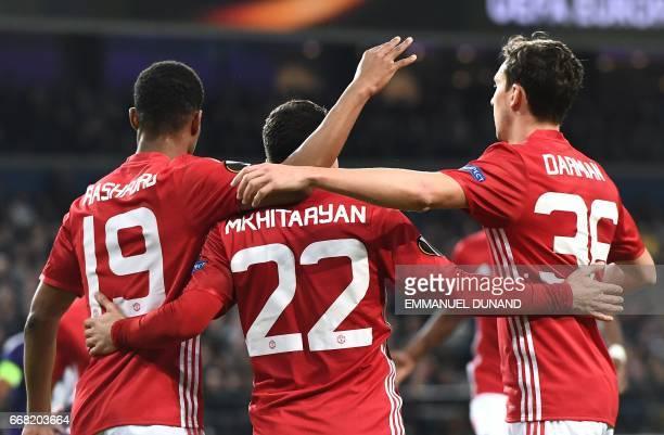 Manchester United's Henrikh Mkhitaryan celebrates with teammates Manchester United's Marcus Rashford and Manchester United's Italian defender Matteo...