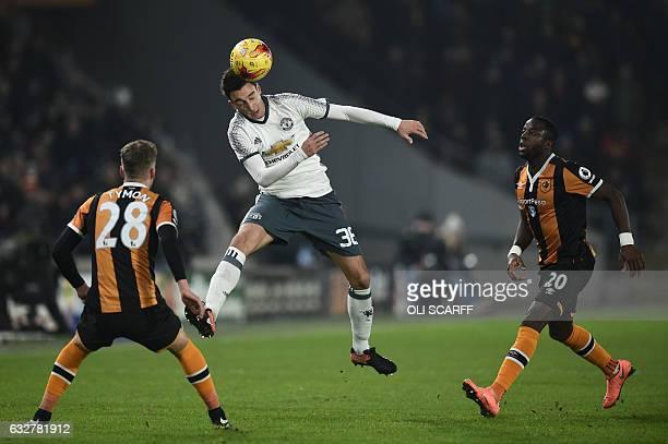 Manchester United's Italian defender Matteo Darmian heads the ball by Hull City's English defender Josh Tymon and Hull City's Norwegian striker Adama...