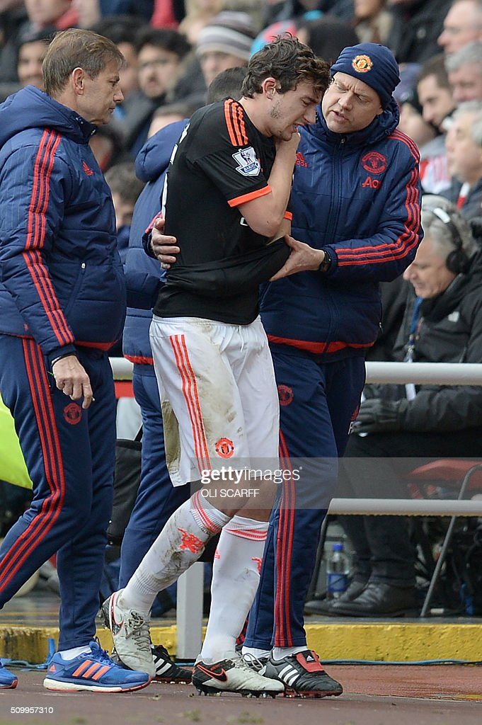 Manchester United's Italian defender Matteo Darmian (C) is escorted off of the pitch after being injured during the English Premier League football match between Sunderland and Manchester United at the Stadium of Light in Sunderland, northeast England on February 13, 2016. / AFP / OLI SCARFF / RESTRICTED TO EDITORIAL USE. No use with unauthorized audio, video, data, fixture lists, club/league logos or 'live' services. Online in-match use limited to 75 images, no video emulation. No use in betting, games or single club/league/player publications. /