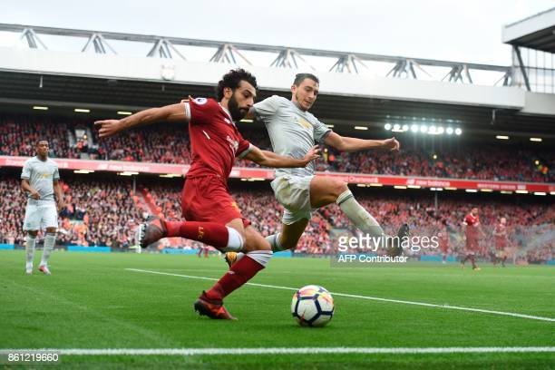 Manchester United's Italian defender Matteo Darmian tries to block a cross from Liverpool's Egyptian midfielder Mohamed Salah during the English...