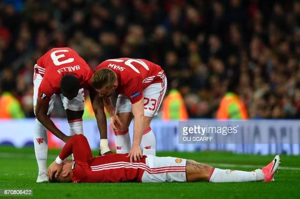 Manchester United's Ivorian defender Eric Bailly and Manchester United's English defender Luke Shaw check on Manchester United's Argentinian defender...