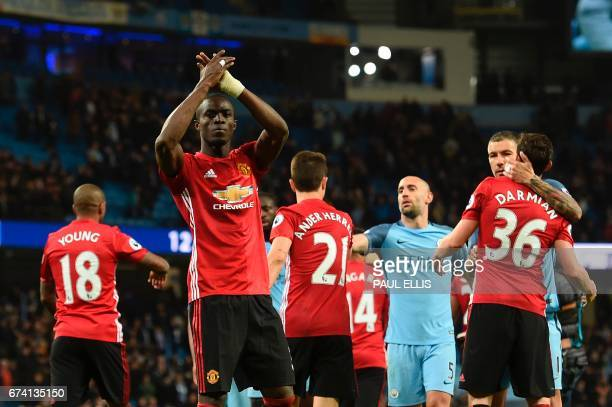 Manchester United's Ivorian defender Eric Bailly applauds their fans at the end of the English Premier League football match between Manchester City...