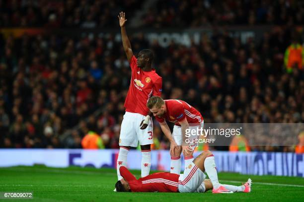 Manchester United's Ivorian defender Eric Bailly calls for the medical team as Manchester United's English defender Luke Shaw checks Manchester...