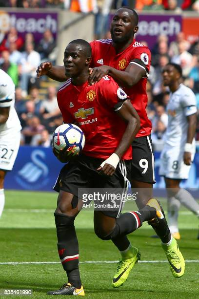 Manchester United's Ivorian defender Eric Bailly celebrates with Manchester United's Belgian striker Romelu Lukaku scoring the team's first goal...