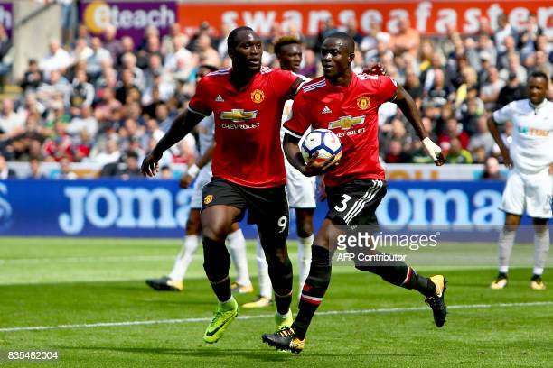 Manchester United's Ivorian defender Eric Bailly celebrates with Manchester United's Belgian striker Romelu Lukaku scoring the team's first goal...