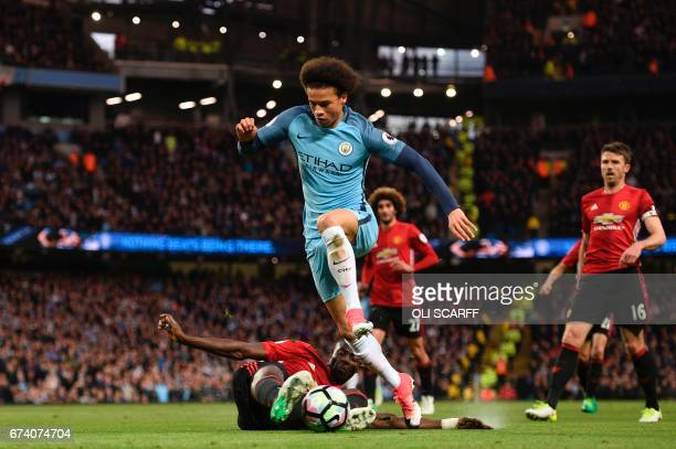 Manchester United's Ivorian defender Eric Bailly goes to ground to cleanly tackle Manchester City's German midfielder Leroy Sane during the English...
