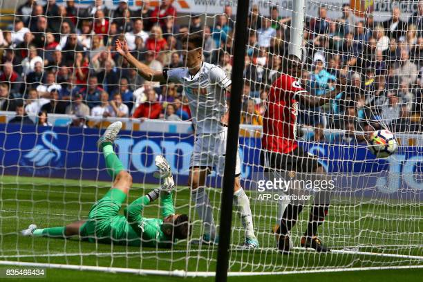 Manchester United's Ivorian defender Eric Bailly scores the team's first goal past Swansea City's Polish goalkeeper Lukasz Fabianski during the...