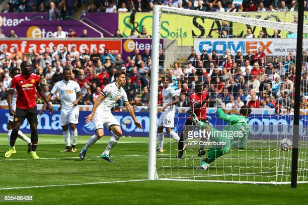 Manchester United's Ivorian defender Eric Bailly scores the team's first goal past Swansea City's Polish goalkeeper Lukasz Fabianski as Manchester...
