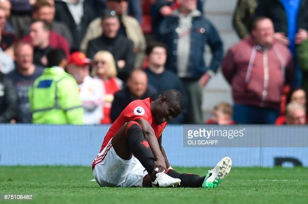 Manchester United's Ivorian defender Eric Bailly sits on the pitch injured during the English Premier League football match between Manchester United...