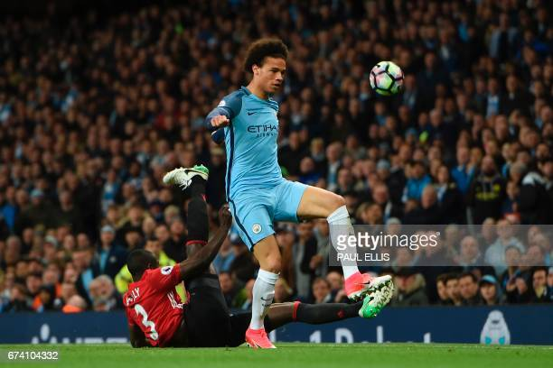 Manchester United's Ivorian defender Eric Bailly slides in to tackle Manchester City's German midfielder Leroy Sane during the English Premier League...