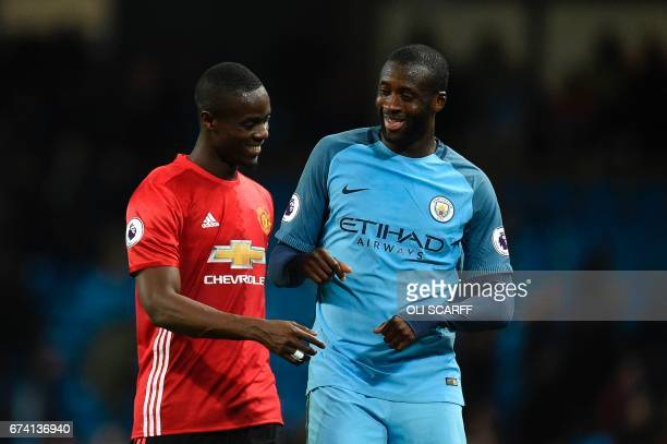 Manchester United's Ivorian defender Eric Bailly talks with Manchester City's Ivorian midfielder Yaya Toure at the end of the English Premier League...