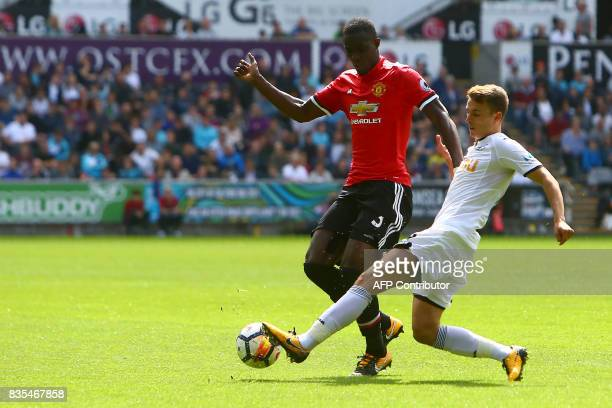 Manchester United's Ivorian defender Eric Bailly vies with Swansea City's English midfielder Tom Carroll during the English Premier League football...
