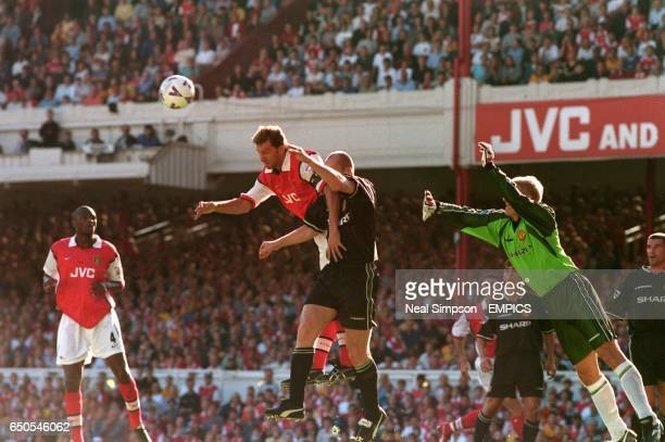 Manchester United's Jaap Stam and goalkeeper Peter Schemeichel are unable to prevent Arsenal's Tony Adams scoring the first goal of the game