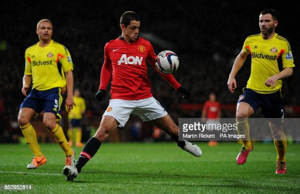 Manchester United's Javier Hernandez controls the ball under pressure from Sunderland's Wes Brown and Phil Bardsley during the Capital One Cup Semi...