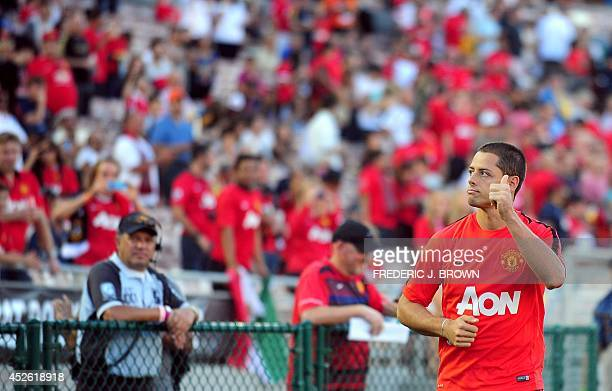 Manchester United's Javier Hernandez gestured to the crowd while appearing for pregame warmups but stayed on the bench for the entire game in their...