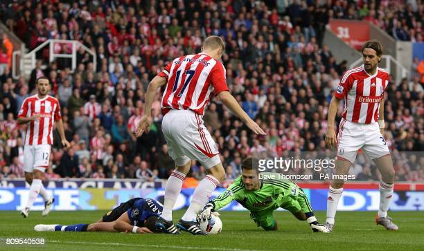 Manchester United's Javier Hernandez lies on the floor injured after being caught by Stoke City's goalkeeper Asmir Begovic