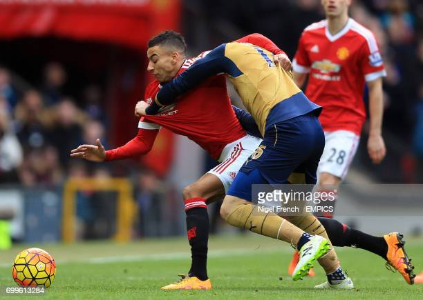 Manchester United's Jesse Lingard is pulled back by Arsenal's Aaron Ramsey