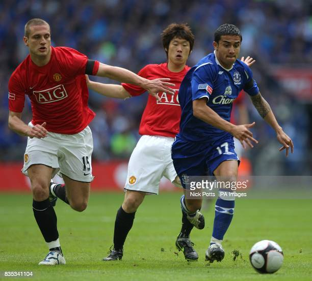 Manchester United's JiSung Park and Nemanja Vidic battle for the ball with Everton's Tim Cahill